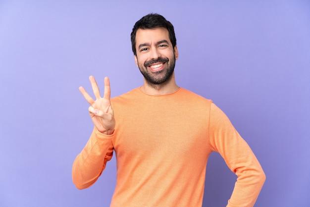 幸せで、指で3を数える孤立した紫色の背景上の白人ハンサムな男