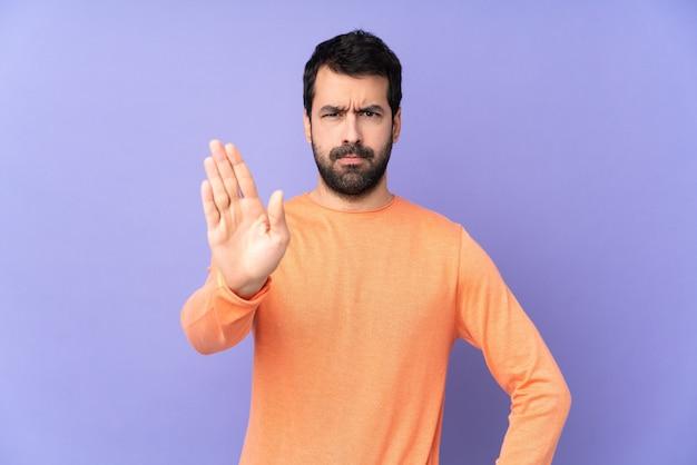 孤立した紫色の停止ジェスチャーを作る白人ハンサムな男