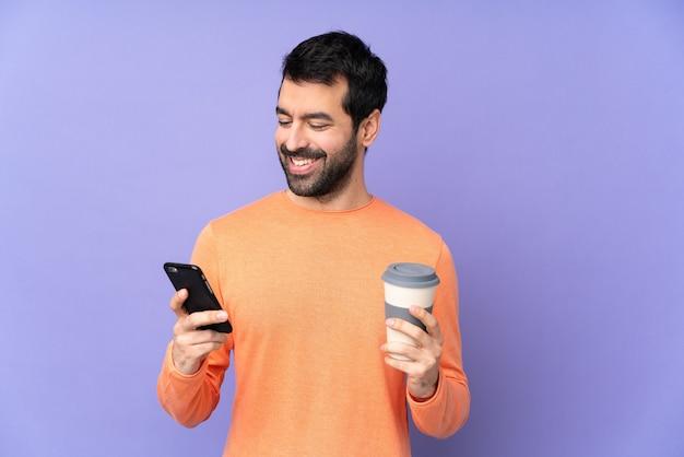 持ち帰り用のコーヒーと携帯電話を保持している孤立した紫色の壁の上の白人ハンサムな男