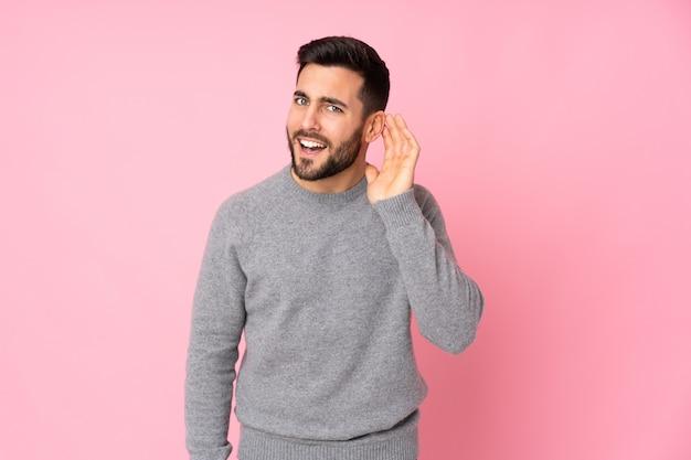 Кавказский красавец над изолированной стеной слушает что-то, положив руку на ухо