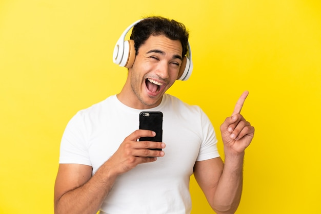 Кавказский красавец на изолированном желтом фоне, слушает музыку с мобильного телефона и поет