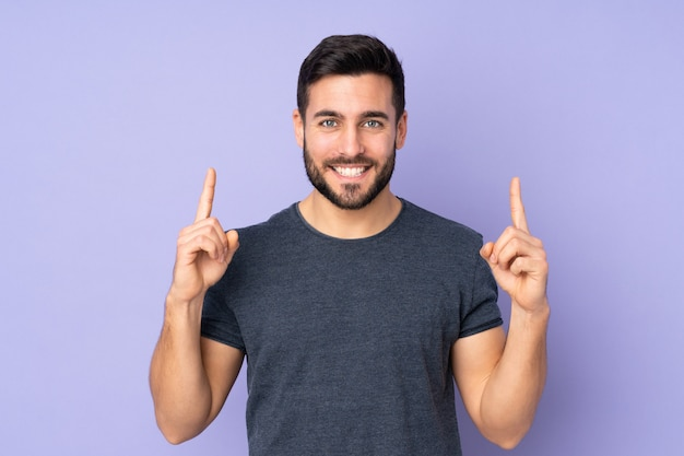 Caucasian handsome man pointing up a great idea over isolated purple wall