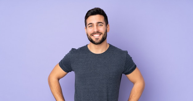 Caucasian handsome man posing with arms at hip and smiling over isolated purple wall