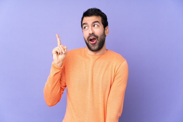 Caucasian handsome man over purple wall intending to realize the solution while lifting a finger up