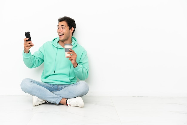 Кавказский красавец сидит на полу, держа кофе на вынос и мобильный