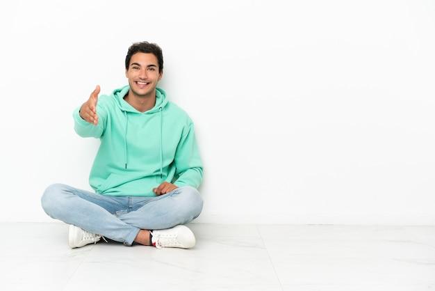 좋은 거래를 마감하기 위해 악수하는 바닥에 앉아 백인 잘 생긴 남자
