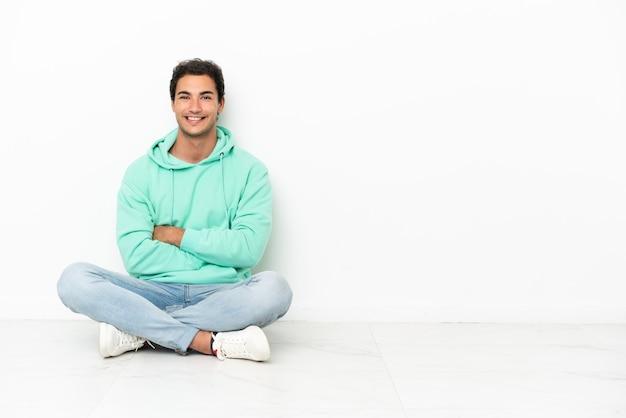 백인 잘생긴 남자가 팔짱을 끼고 바닥에 앉아 기대하고 있다