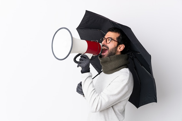 Caucasian handsome man with beard holding an umbrella over isolated white wall shouting through a megaphone