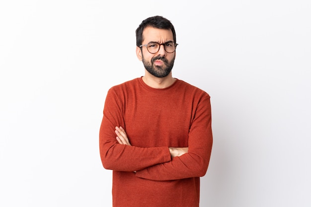 Caucasian handsome man with beard over isolated white wall feeling upset