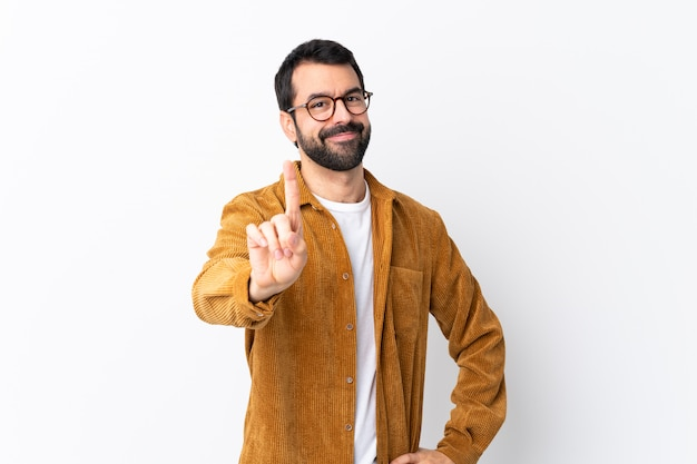 Caucasian handsome man with beard wearing a corduroy jacket over white showing and lifting a finger