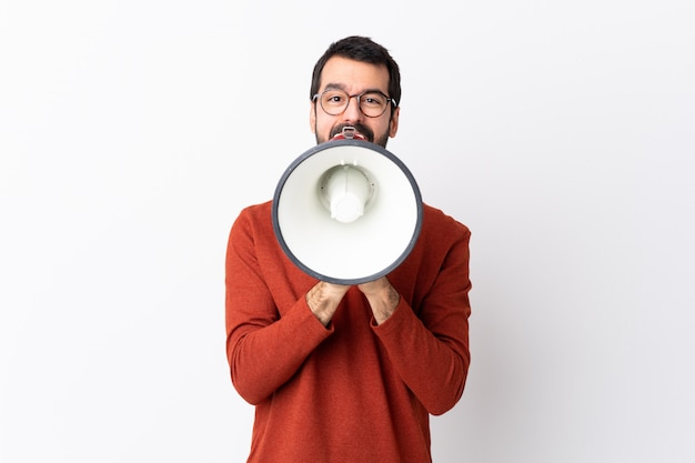 Caucasian handsome man with beard over white shouting through a megaphone