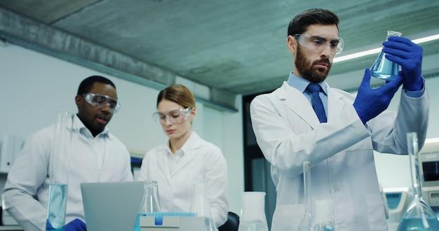 彼の多民族の同僚が現場で話しながら試験管内のいくつかの液体の分析を行う白人のハンサムな医療研究所男性労働者。