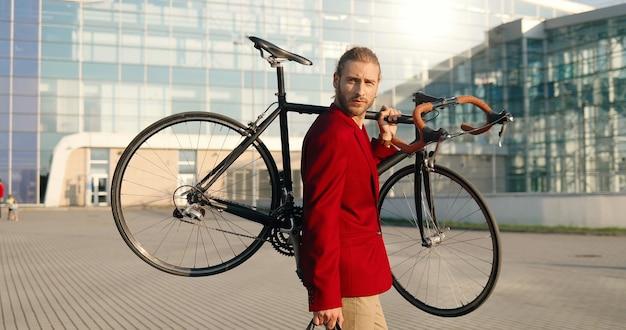 白人のハンサムな若いスタイリッシュな男は、屋外を歩き、自転車を肩に乗せて赤いカジュアルジャケットを着ています。都市景観。背景にモダンなガラスの建物。自転車を散歩して保持している男性ライダー。