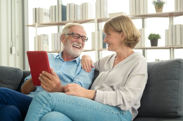 Caucasian happy seniors elderly are video calling to family or friends, relax at home, smiling healthy senior retired grandparents, older grandparent technology concept