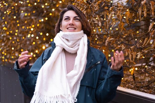 暖かいスカーフを身に着けて、雪と冬を楽しんでいる白人の幸せな笑顔の女性