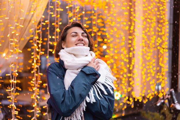 Donna sorridente felice caucasica che gode della neve e dell'inverno, indossando sciarpa calda