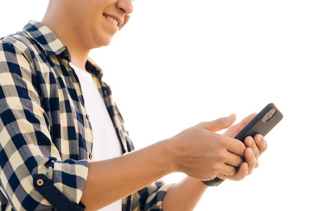 シャツを着た白人の流行に敏感な男性は、ダウンタウンの路上でスマートフォンを使用しています。彼は微笑んで成功しているように見えます。彼は自分のデバイスでウェブを閲覧しています