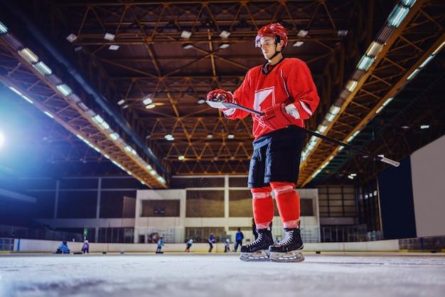 Кавказский хоккеист, стоя на льду и снимающий лед с палки. интерьер зала. зимние виды спорта.