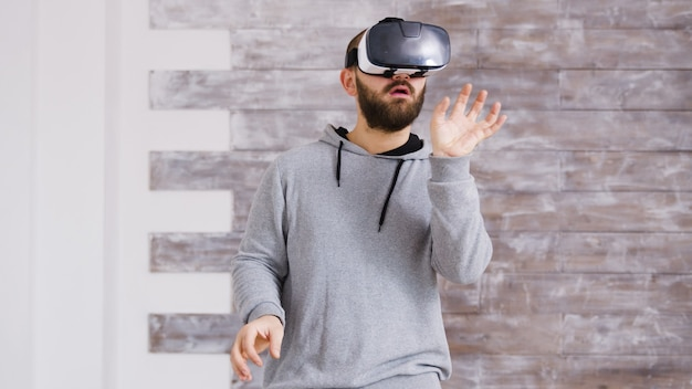 Caucasian home designer using virtual reality goggles inside of an empty apartment to decorate it in cyberspace