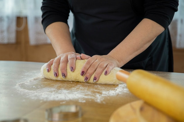 Caucasian housewife in a black apron rolls the dough with her hands. close-up.