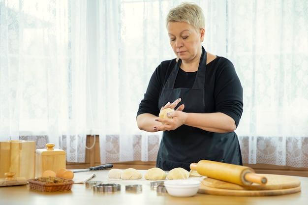 白人の主婦は小麦粉をまぶしたテーブルの上に生の生地からケーキを形成します