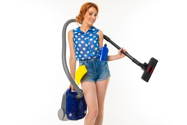 Caucasian housewife with cleaning products and a vacuum cleaner in her hands goes to clean the dirt on a white background.