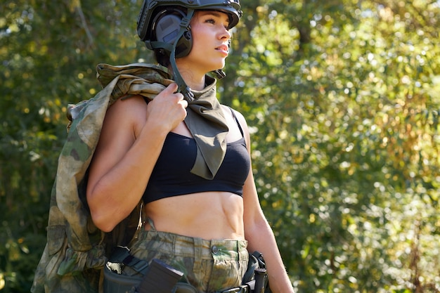 スポーティーなトップの白人ハンター女性は森の中で動物を探しています