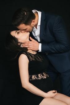Caucasian husband kissing his pregnant girl on black background