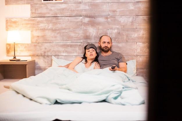 Marito e moglie caucasici che indossano un pigiama mentre guardano la tv prima di andare a dormire.