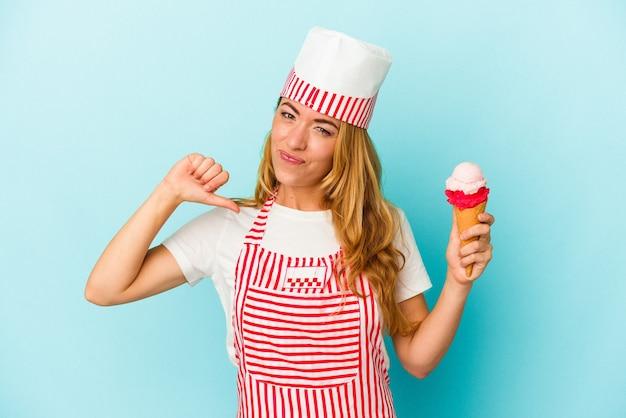 青い背景に分離されたアイスクリームを保持している白人のアイスクリームメーカーの女性は、誇りと自信を持っています。