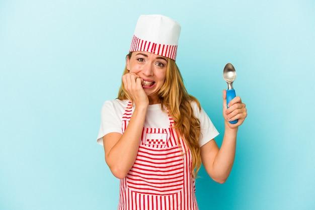 파란색 배경에 격리된 아이스크림 국자를 들고 있는 백인 아이스크림 제조사 여성은 손톱을 물어뜯고 긴장하고 매우 불안해합니다.