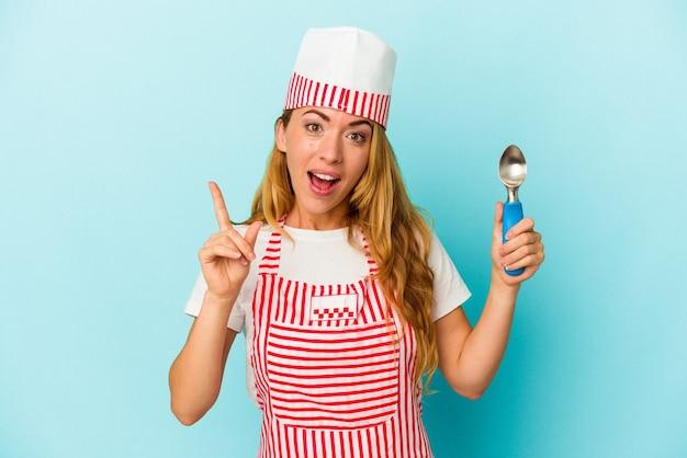 アイデア、インスピレーションのコンセプトを持つ青い背景で隔離のアイスクリームスクープを保持している白人のアイスクリームメーカーの女性。