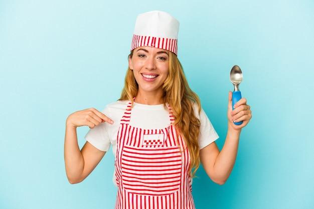 誇りと自信を持って、シャツのコピースペースを手で指している青い背景の人に分離されたアイスクリームスクープを保持している白人のアイスクリームメーカーの女性