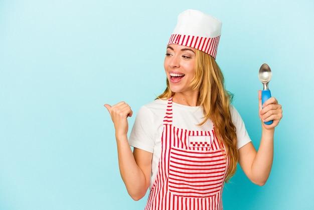 青い背景のポイントで隔離されたアイスクリームスクープを親指の指で離れて、笑ってのんきなアイスクリームメーカーの女性。