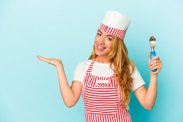 手のひらにコピースペースを示し、腰に別の手を保持している青い背景で隔離のアイスクリームスクープを保持している白人のアイスクリームメーカーの女性。