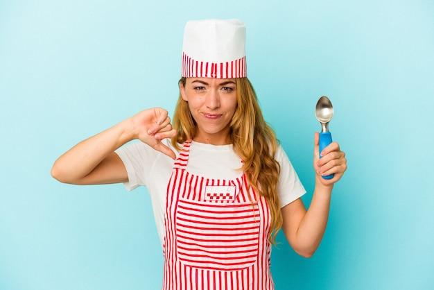 嫌いなジェスチャーを示す青い背景で隔離のアイスクリームスクープを保持している白人のアイスクリームメーカーの女性は、親指を下に向けます。不一致の概念。