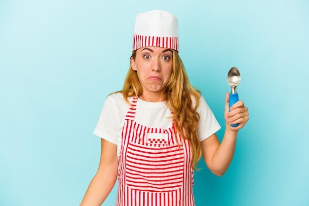 青い背景に分離されたアイスクリームスクープを保持している白人のアイスクリームメーカーの女性は、肩をすくめ、目を開けて混乱しています。
