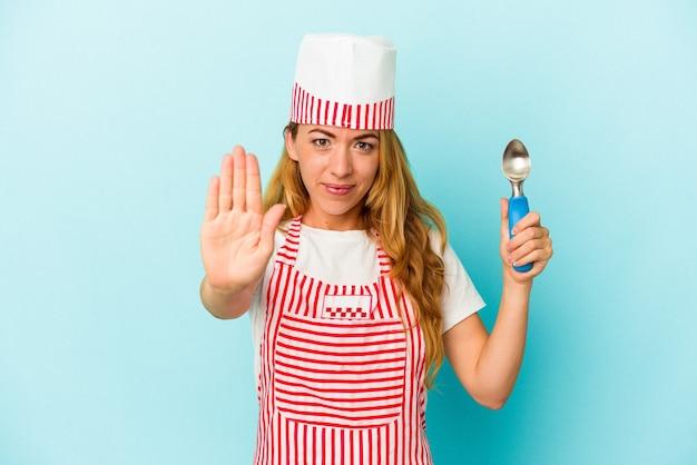 青い背景で隔離のアイスクリームスクープを保持している白人のアイスクリームメーカーの女性は、一時停止の標識を示している手を伸ばして立って、あなたを防ぎます。
