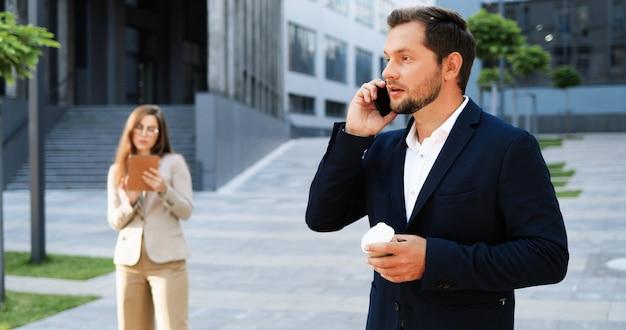 携帯電話で話し、通りで朝に温かい飲み物をすすりながら白人のうれしそうな若いスタイリッシュな男。携帯電話で話し、コーヒーを飲むハンサムな幸せな男性。外側。