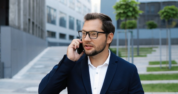 通りを歩いて、携帯電話で話し、朝に温かい飲み物をすすりながら白人のうれしそうな若いスタイリッシュな男。携帯電話で話し、散歩しながらコーヒーを飲むハンサムな幸せな男性。