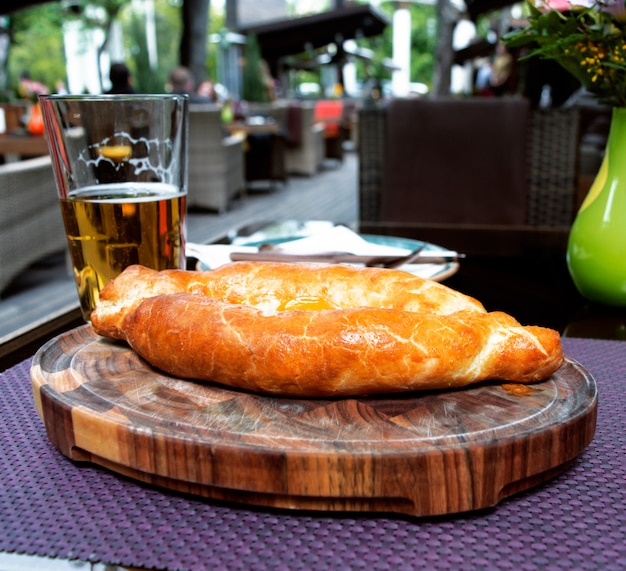 Caucasian khachapuri with a glass of beer in a restaurant