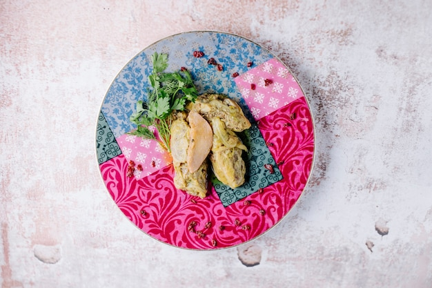 Caucasian khingali with parsley and apple slice in a colorful plate.