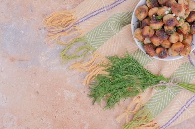 Ripieni khinkal caucasici fritti e serviti con erbe tritate.
