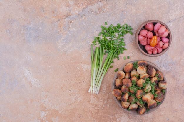 Ripieni khinkal caucasici in una ciotola di legno fritti e serviti con erbe e cibi marinati.