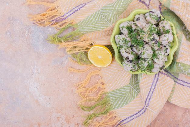 Кавказское тесто хинкали в зеленой тарелке с зеленью и лимоном