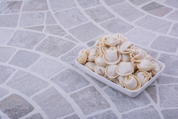 회색 표면에 흰색 그릇에 백인 khinkali 반죽