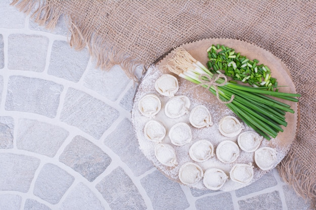 Кавказское тесто хинкали на деревянной доске с зеленым луком