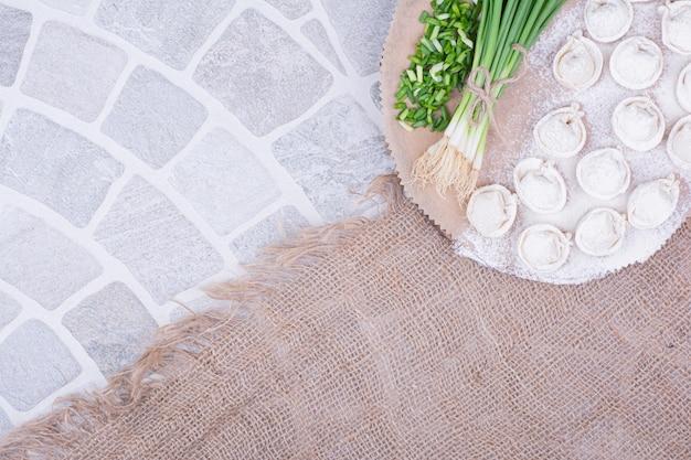 Pasta khinkali caucasica su una tavola di legno con cipolle verdi