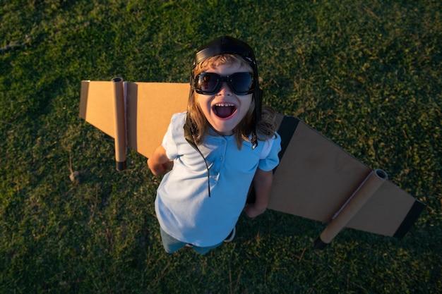 잔디가 무성한 여름 언덕 밖의 하늘 배경에서 장난감 비행기를 가지고 노는 백인 아이. 행복한 미래 개념을 꿈꾸고 있습니다.