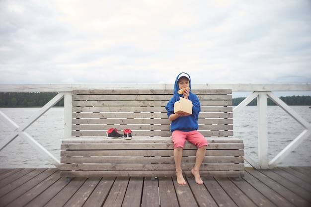 Caucasian kid sits on pier and eating pizza